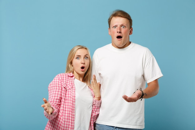 Jovem casal chocado, amigos, homem e mulher, em camisetas brancas rosa vazias posando