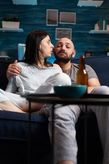 Jovem casal chocado e surpreso assistindo a um documentário na tv