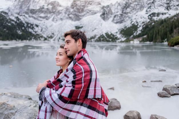 Jovem casal coberto com cobertor brilhante está de pé na frente do lago das montanhas congelado