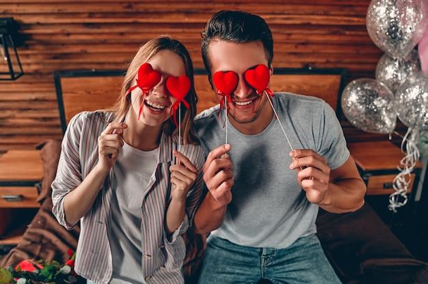 Jovem casal cobre os olhos com corações enquanto comemora o dia dos namorados.