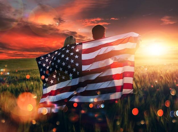 Jovem casal com a bandeira americana em um campo de trigo ao pôr do sol, comemorando o dia da independência