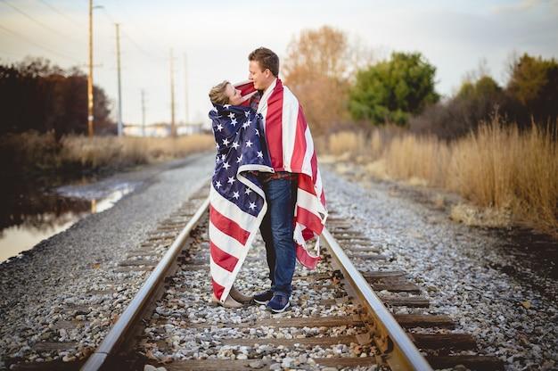 Jovem casal com a bandeira americana pendurada nos ombros em pé na ferrovia