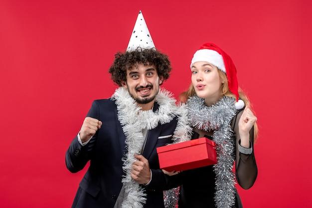 Jovem casal com ano novo presente na festa de amor de natal no piso vermelho