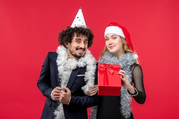 Jovem casal com ano novo presente na mesa vermelha, feriado de amor de natal
