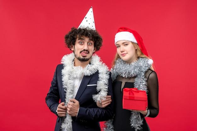 Jovem casal com ano novo presente na parede vermelha festa de amor de natal