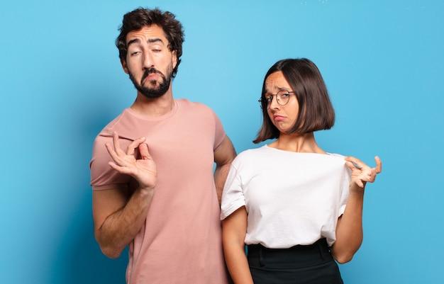 Jovem casal com ar arrogante, bem-sucedido, positivo e orgulhoso, apontando para si mesmo