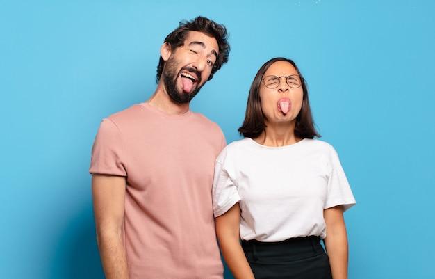 Jovem casal com atitude alegre, despreocupada, rebelde, brincando e mostrando a língua, se divertindo