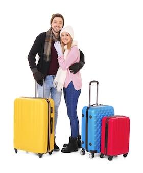 Jovem casal com bagagem em fundo branco. pronto para as férias de inverno