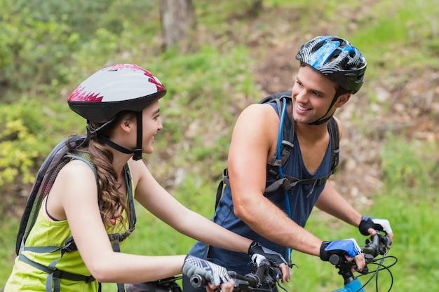 Jovem casal com bicicletas, olhando um ao outro