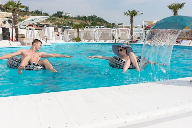 Jovem casal com bóia salva-vidas inflável tentando alcançar suas mãos enquanto desfruta da piscina em um resort.