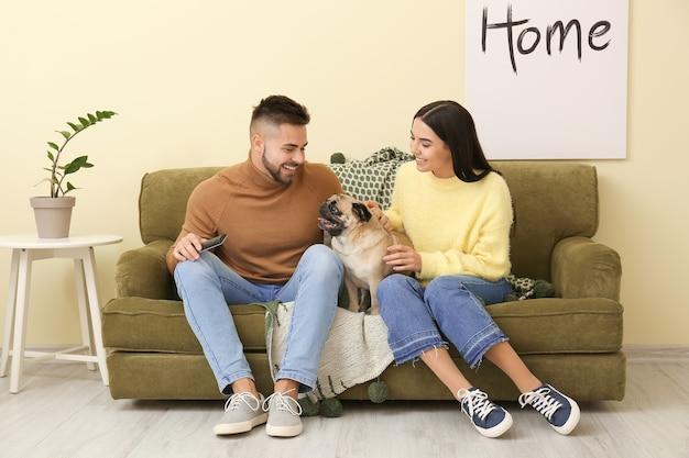 Jovem casal com cachorro assistindo tv enquanto está sentado no sofá em casa