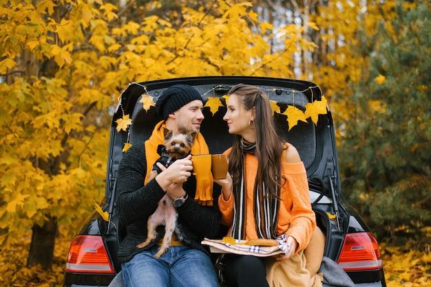 Jovem casal com cachorro sentado no porta-malas de um carro