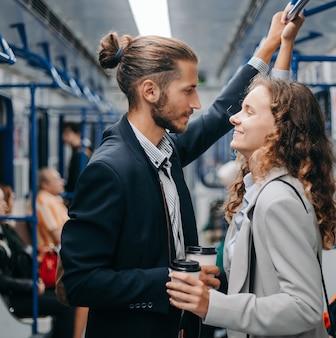 Jovem casal com café para viagem parado no vagão do metrô