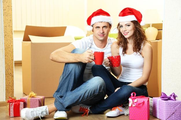 Jovem casal com caixas na nova casa comemorando o ano novo
