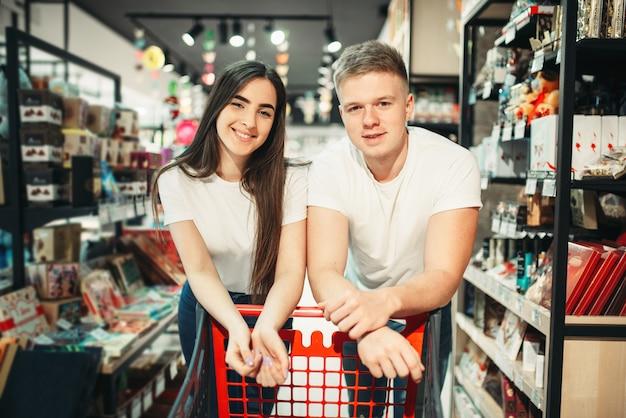Jovem casal com carrinho, departamento de confeitaria no mercado. clientes na loja de alimentos, compradores no supermercado