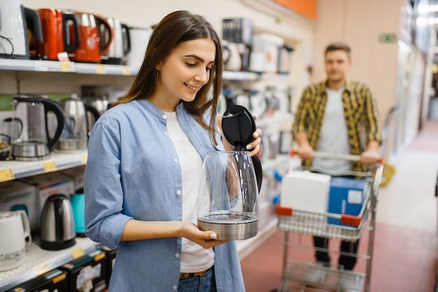 Jovem casal com carrinho procurando chaleira elétrica na loja de eletrônicos. homem e mulher comprando eletrodomésticos no mercado