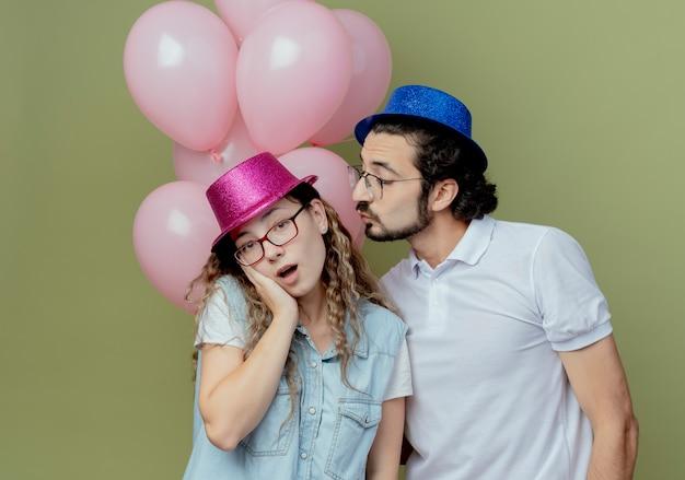 Jovem casal com chapéu rosa e azul parado na frente da garota dos balões colocando a mão na bochecha