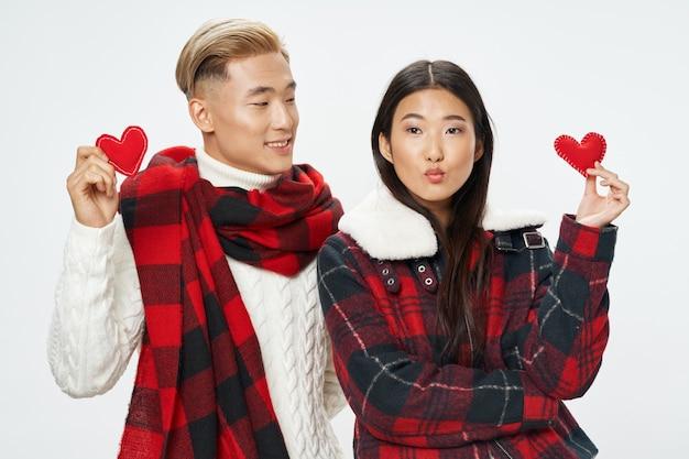 Jovem casal com corações nas mãos com roupas de inverno.