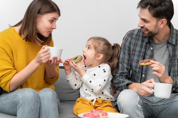 Jovem casal com criança comendo donuts
