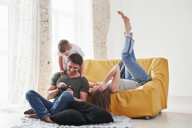 Jovem casal com criança juntos olhando as fotos.