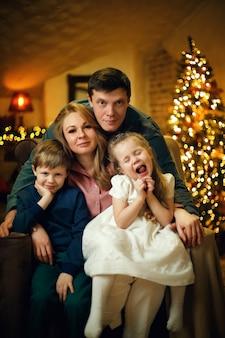 Jovem casal com dois filhos posando em uma cadeira em um interior de natal com uma árvore de natal
