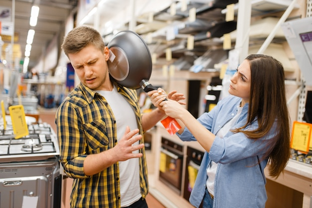 Jovem casal com frigideira na loja de eletrônicos. homem e mulher comprando eletrodomésticos no mercado