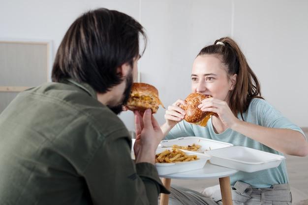 Jovem casal com hambúrgueres e caixas, movendo-se no novo conceito de apartamento, nova casa e realocação.