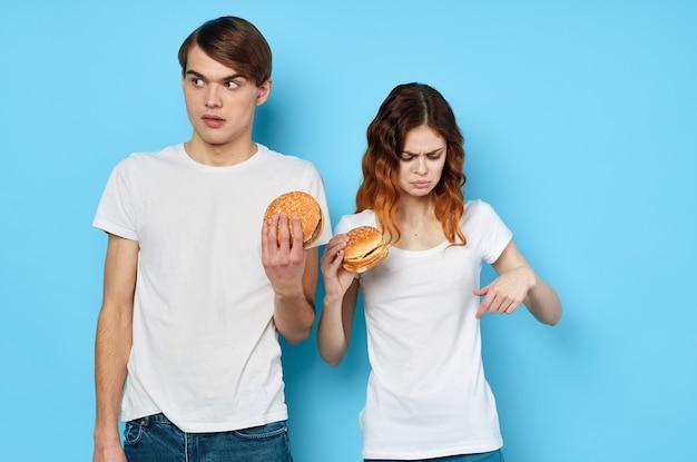 Jovem casal com hambúrgueres nas mãos