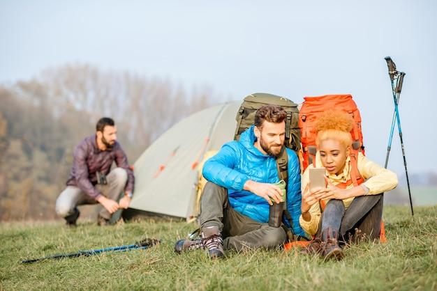 Jovem casal com jaquetas coloridas e mochilas se divertindo com o smartphone sentado no gramado verde perto do acampamento