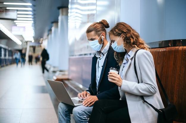 Jovem casal com laptop na plataforma do metrô