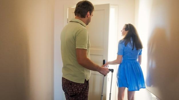 Jovem casal com malas andando em seu quarto de hotel de férias.
