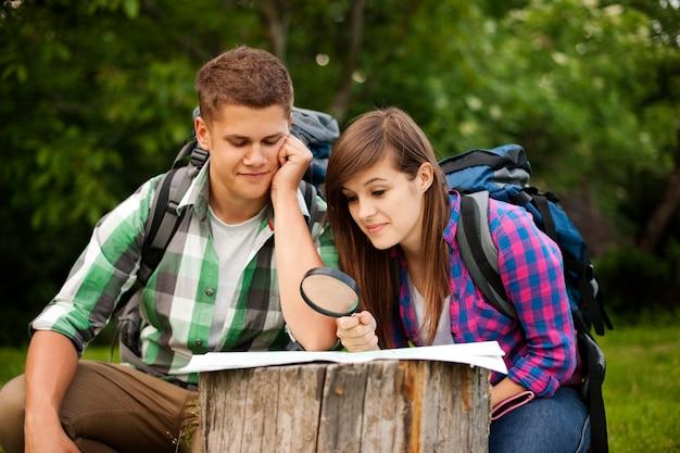 Jovem casal com mapa na floresta