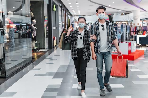 Jovem casal com máscara de proteção segurando várias sacolas de papel andando no corredor de um grande shopping center