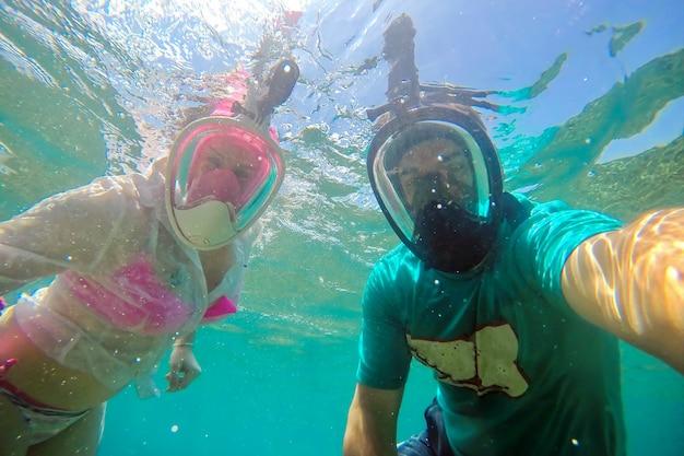 Jovem casal com máscaras faciais para mergulho com snorkel fazendo selfie debaixo d'água