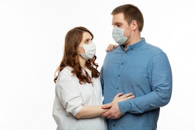 Jovem casal com máscaras médicas. uma mulher grávida com seu marido estão se abraçando.