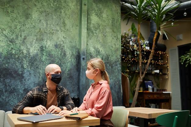 Jovem casal com máscaras protetoras discutindo algo durante uma reunião no café