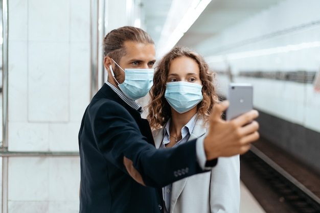 Jovem casal com máscaras protetoras tirando selfies no metrô