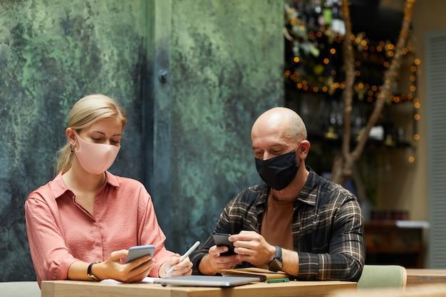 Jovem casal com máscaras protetoras usando telefones celulares durante o almoço no café
