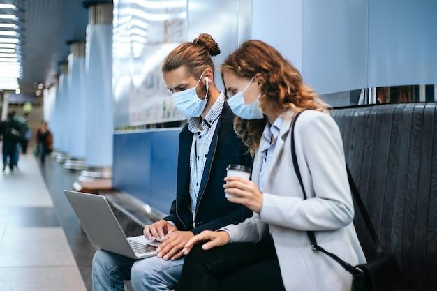 Jovem casal com máscaras protetoras usando um laptop na plataforma do metrô