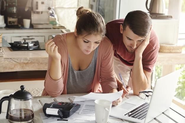Jovem casal com muitas dívidas fazendo papelada juntos, revisando suas contas, planejando o orçamento da família e calculando as finanças na mesa da cozinha com papéis