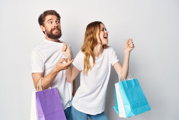 Jovem casal com pacotes nas mãos comprando entretenimento