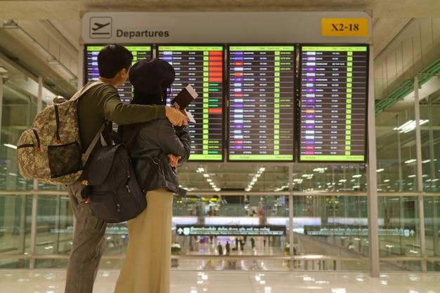 Jovem casal com passaporte nas mãos, olhando para a tela de informações de voo embaçada no aeroporto