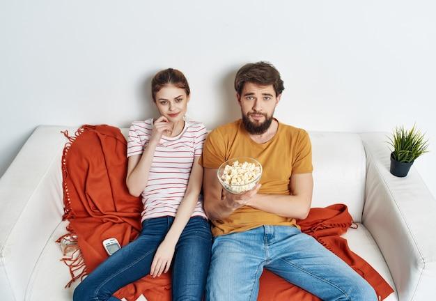 Jovem casal com pipoca sentado no sofá assistindo filme de cinema