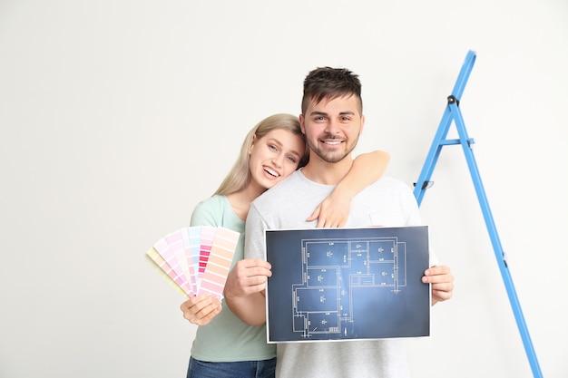 Jovem casal com planta de casa e amostras de cores em branco