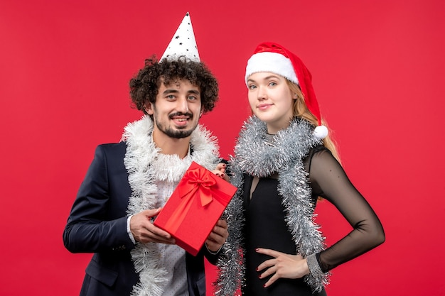Jovem casal com presente comemorando na parede vermelha festa de amor de natal