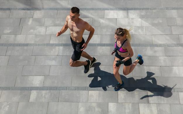 Jovem casal com roupa esportiva, fazendo exercícios matinais ao ar livre.