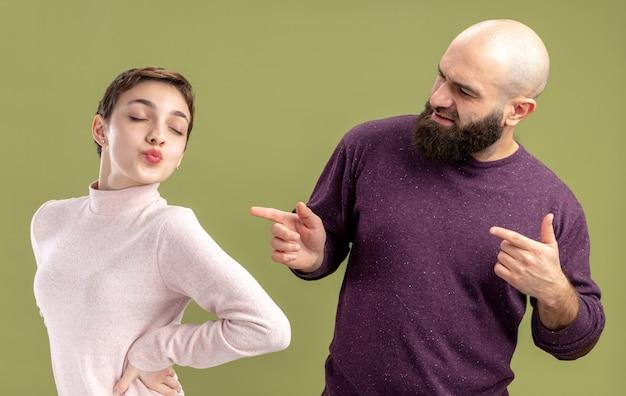 Jovem casal com roupas casuais barbudo apontando com o dedo indicador para sua namorada com cabelo curto comemorando o dia dos namorados em pé sobre a parede verde