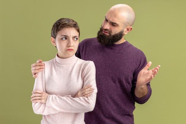 Jovem casal com roupas casuais barbudo homem ficando confuso olhando para sua namorada séria com cabelo curto conceito dia dos namorados em pé sobre a parede verde