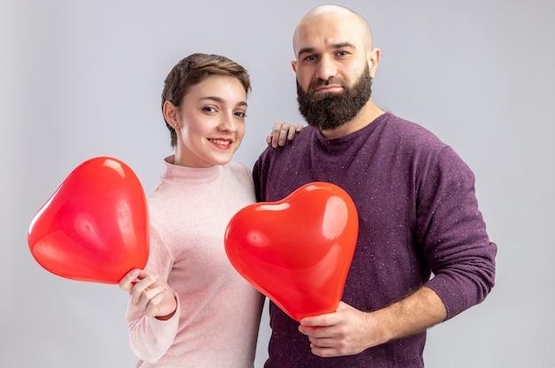 Jovem casal com roupas casuais, homem e mulher segurando balões em forma de coração, olhando para a câmera, feliz e alegre, sorrindo celebrando o dia dos namorados em pé sobre uma parede branca