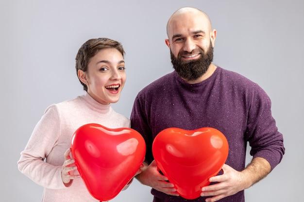 Jovem casal com roupas casuais homem e mulher segurando balões em forma de coração, olhando para a câmera, feliz e surpreso, comemorando o dia dos namorados em pé sobre um fundo branco